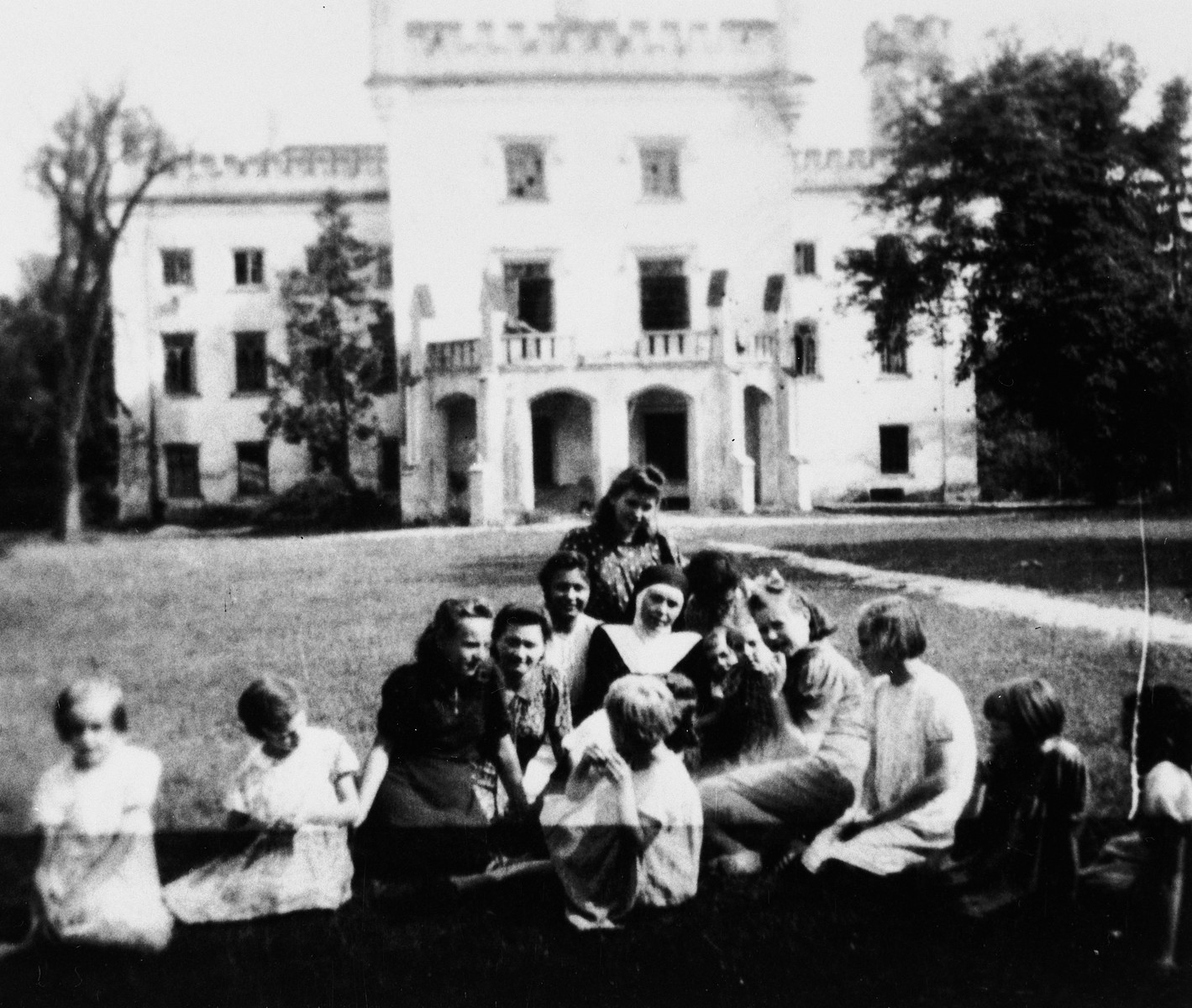 Sister Alma sits on the grass of a convent school in Stara Wies surrounded by four women and six small girls.  Halina Wroncberg, living under the assumed name of Halina Chmielewska, is second from the left.  German officers occupied the left wing of the building.