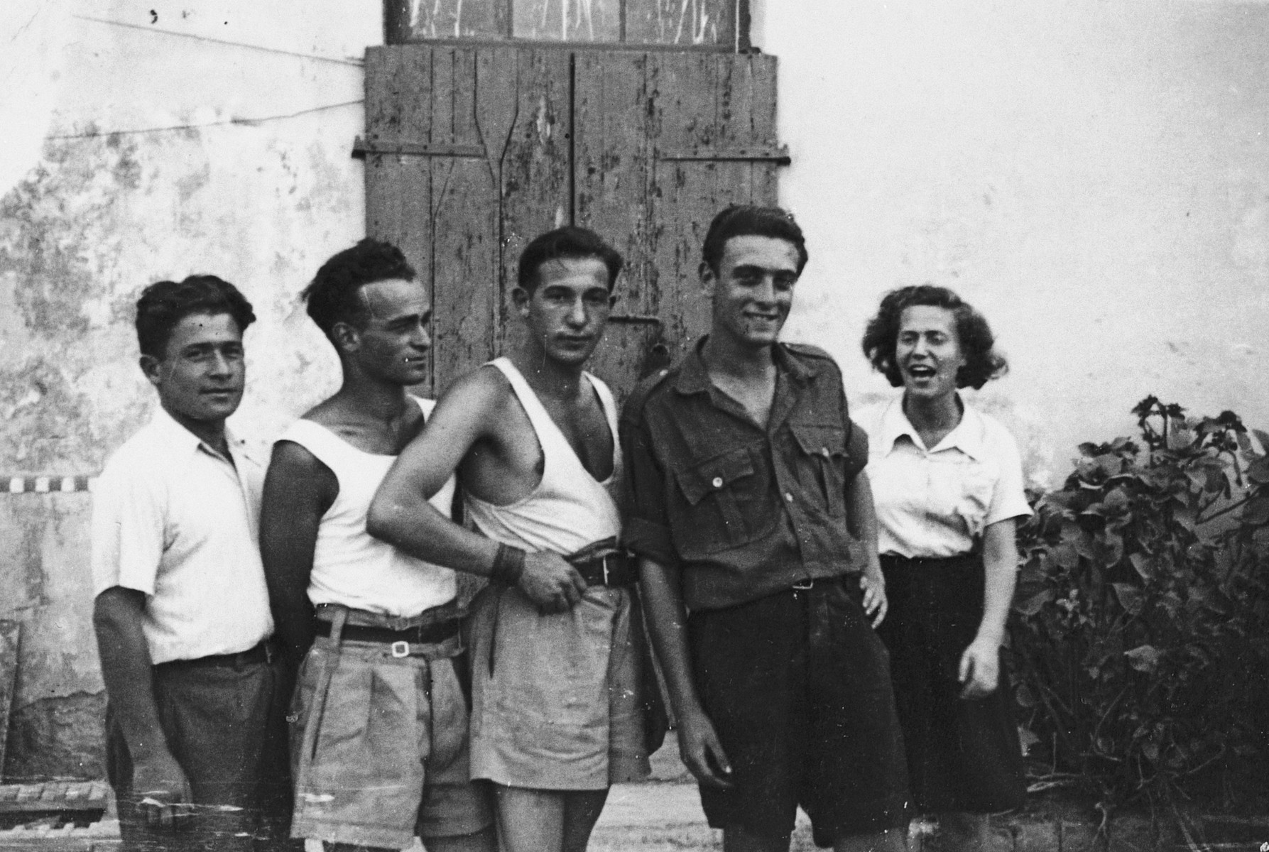 Five members of Kibbutz Maestro pose together outside a building.  Boris Shub is pictured second from the right.