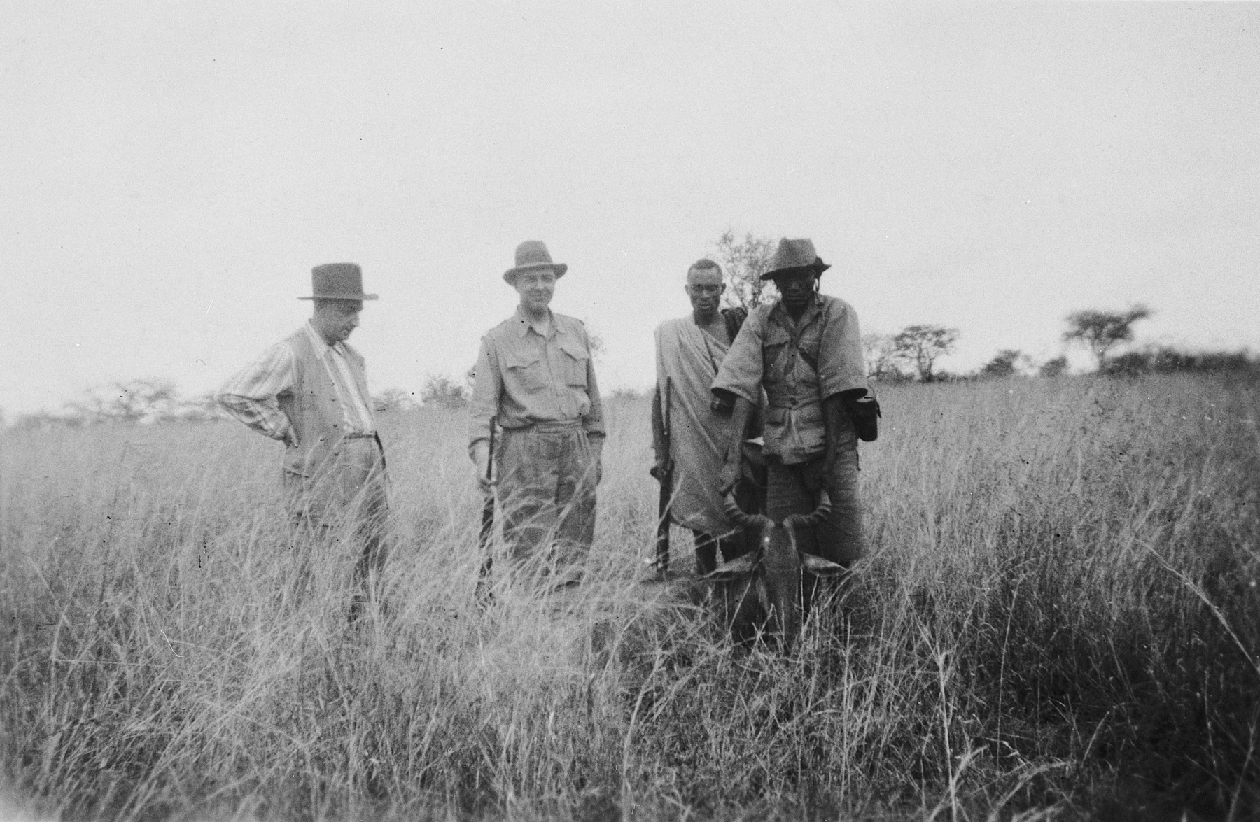 German Jewish refugee Heinrich Weyl poses with friends and an African employee in the bush while on a safari in Kenya.