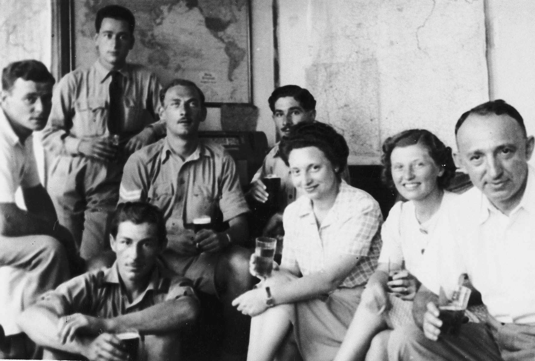 British soldiers gather in the apartment of Ruth and Heinrich Weyl to listen to war news on their radio.