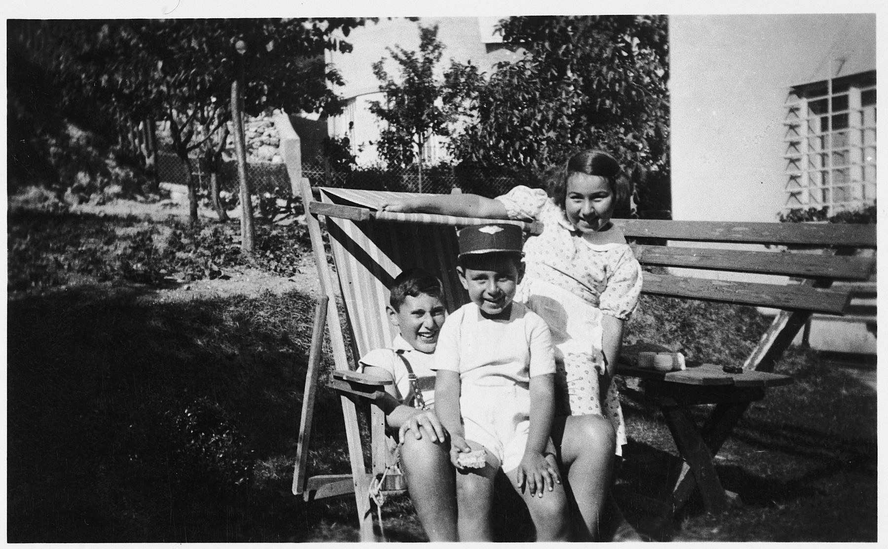 Three Jewish children share a lawn chair.  Pictured are Charlotte and Victor Neumann and their cousin, Erich Butchovits.