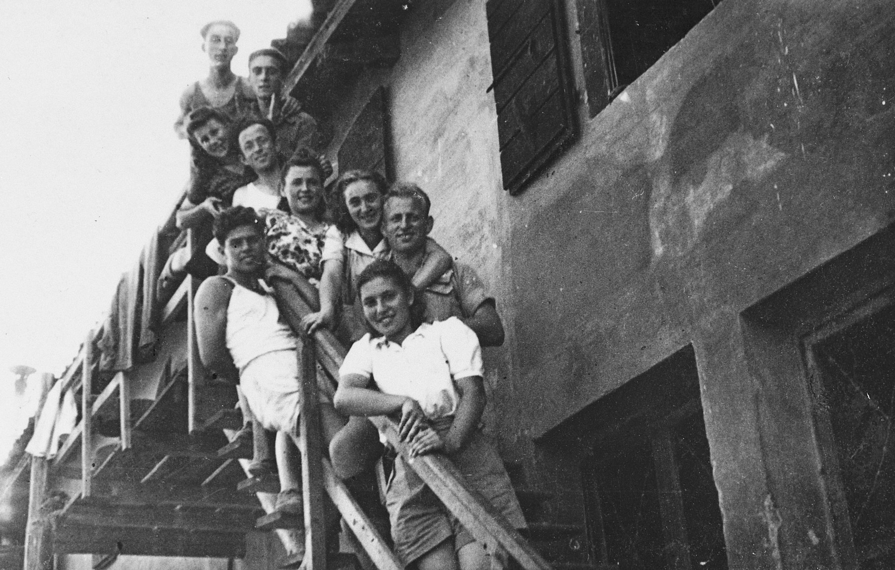 Members of Kibbutz Maestro pose by the railing of the outside steps to a building.  Among those pictured is Boris Shub.