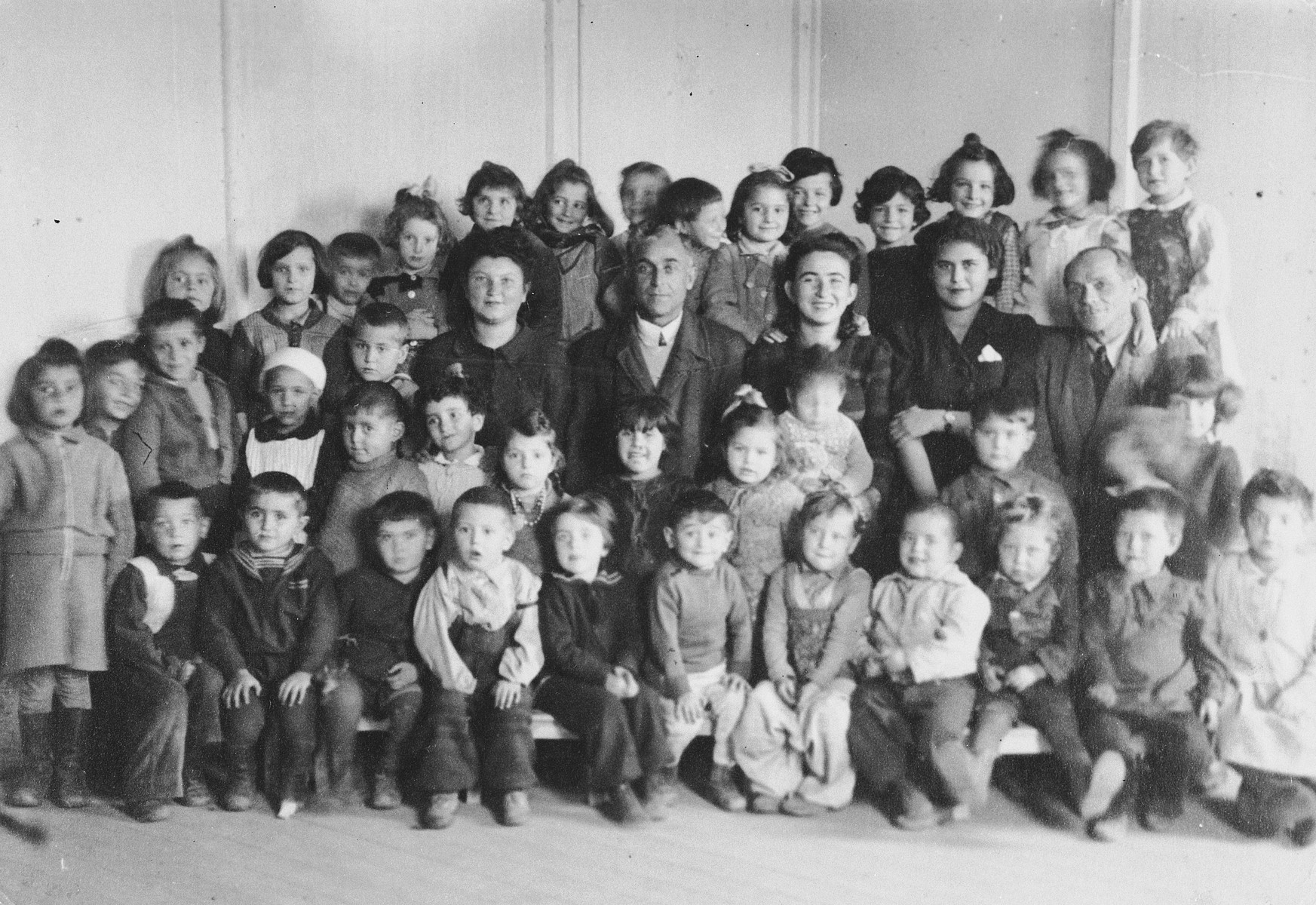 Teachers and young children in the elementary school in the Ainring displaced persons camp.  Among those pictured is the teacher, Sara Michlowitz (Muschel), center row, third from the right.  Also pictured is Rachel Yudkowitz (seventh child standing from the left , wearing a bow in her hair).