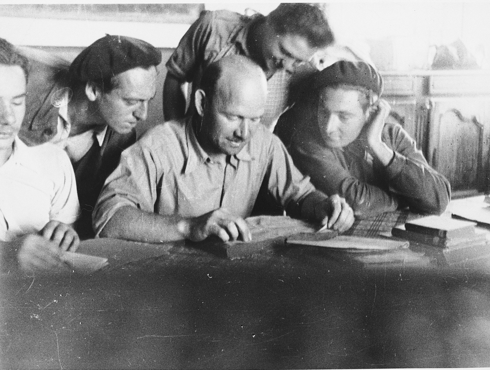 Members of the leadership of the Eclaireurs Israelites de France (Jewish Scouts) look at a book together.  Among those pictured is F. Hammel (center).  The EIF joined forces with the Mouvement de la Jeunesse Sioniste in 1943.