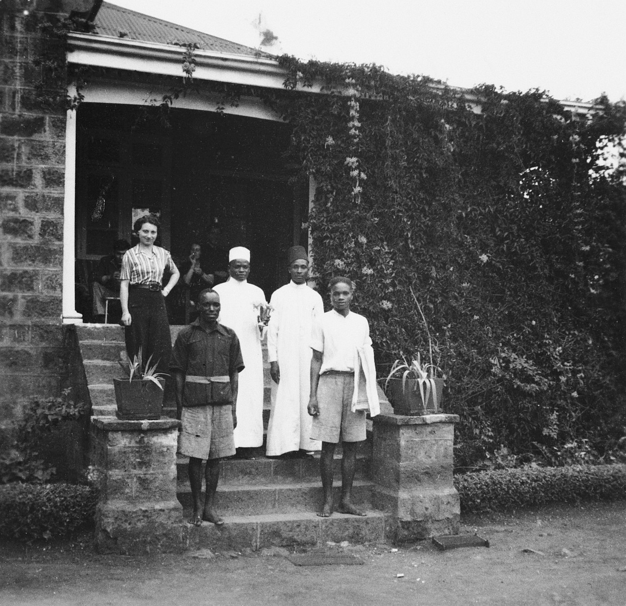German Jewish refugee Ruth Weyl poses with her African staff on the steps of her boarding house in Nairobi, Kenya.