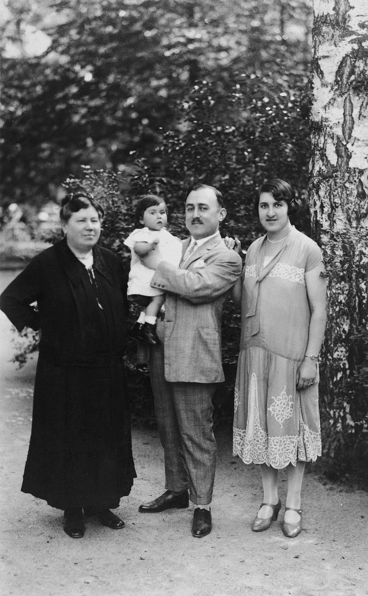 Three generations of a Jewish Slovak family pose for a portrait in a park.  From left to right are Rosa Deutsch, Leopold Neumann holding his baby daughter Charlotte, and Hilde Neumann.