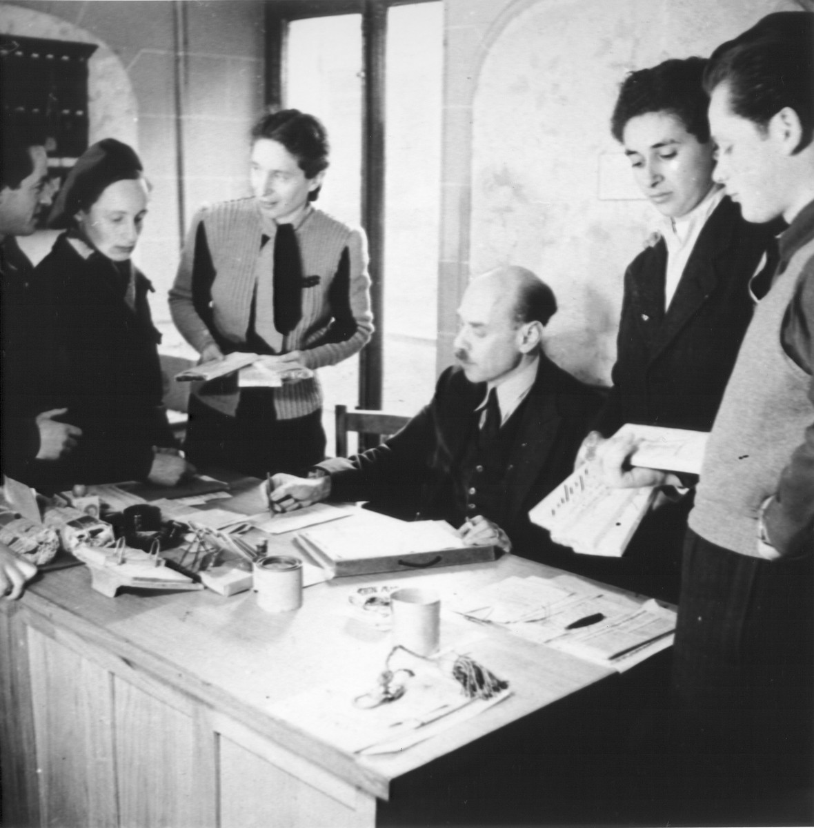 Jewish DP youth living at the OSE (Oeuvre de Secours aux Enfants) children's home on the rue Rollin in Paris, meet with the director of the home in his office.  Among those pictured are: M. Adler, the director of the home and his wife (center).  The Adlers were Jewish refugees from Germany.