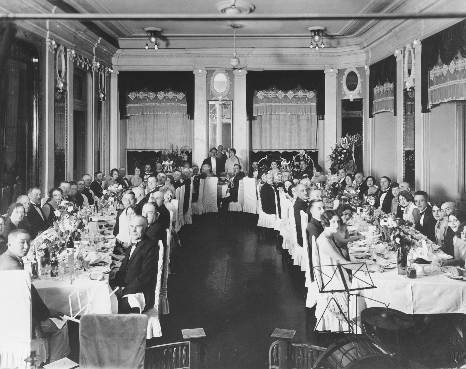 Guests attend a banquet in Harbin, China to celebrate the wedding anniversary of Isaac and Manya Soskin.  Isaac Soskin was the brother of Betia (Soskin) Faingersch.