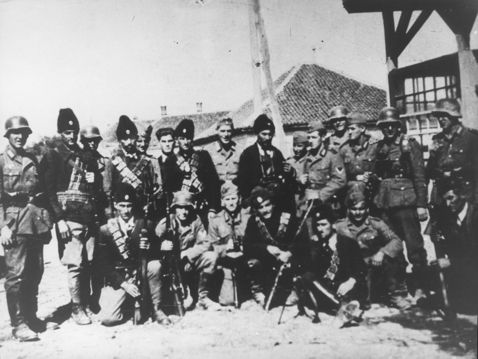 A group of Chetniks pose with German soldiers in an unidentified village in Serbia.
