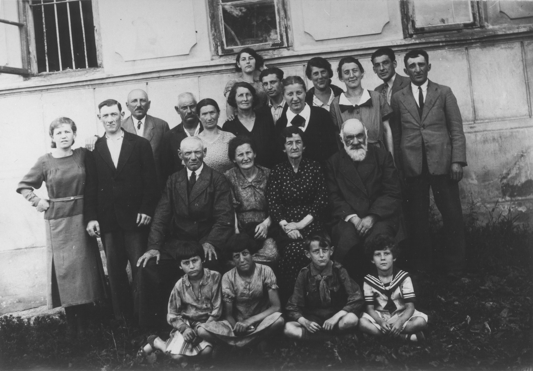 Group portrait of an extended Jewish family outside their home in Piotrkow Trybunalski, Poland.  Pictured are members of the Wolrajch family.  The photograph was taken on the occasion of the visit of Helen Tolep from the U.S.  Pictured in the front row (left to right): two Kudich children, Chiemic and Ginka Wolrajch.  Second row: Reuven and Zelda Fish and Rachel and Moishe Wolrajch.  Third row: Avrum's wife, Avrum Wolrajch, David Fish, Moishe Kudich, Geitel Kudich, Sheindl Fish (top), Sheindl Kudich, David Fish, Helen Tolep, Rachel Wolrajch, Chia Sura Wolrajch, Joel Wolrajch and Josef Wolrajch.