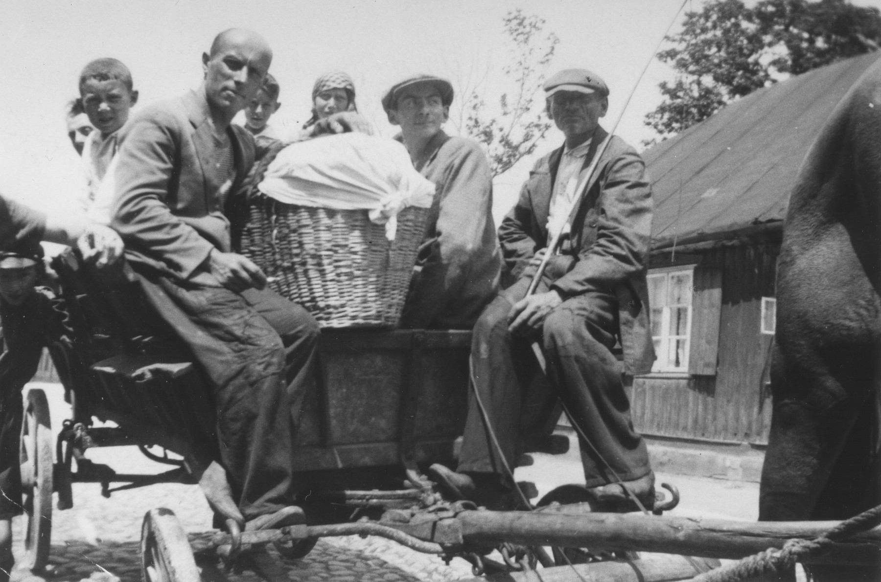 A group of Jews rides on the back of a horse-drawn wagon in Piotrkow Trybunalski, Poland.  The group is on their way to a neighboring town where the man with the basket will sell his wares.  Among those pictured are Reuven Fish, Shaya Wolrajch, Hersh Lieb Wolrajch, Chiemic and Wolf.