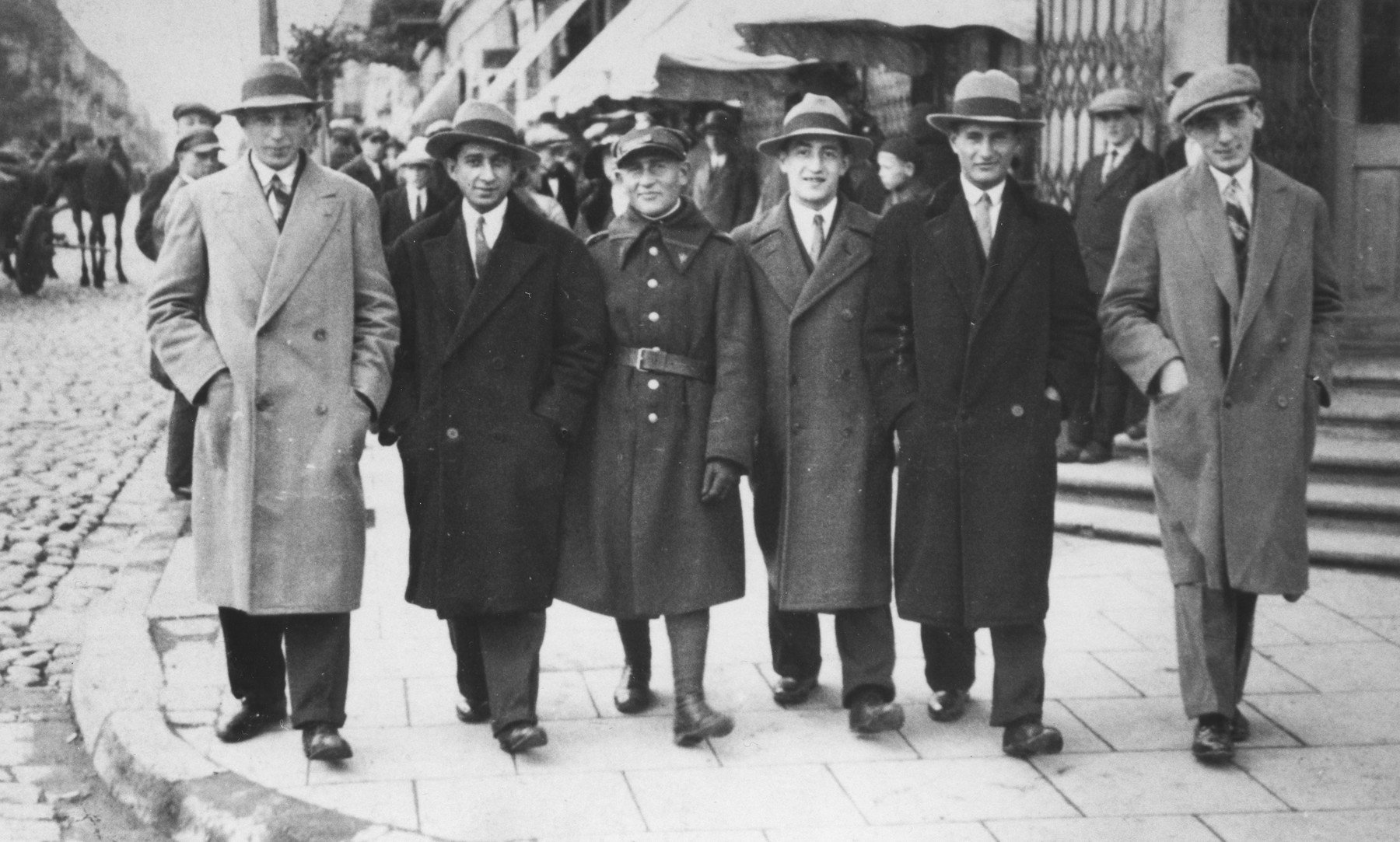 A group of Jewish friends walk along the main street of Piotrkow Trybunalski.  Pictured from left to right are: Weinberg, Schmel Lieberman, Itchak Rosencweig, Schmuel David Horn, and Boruch Hersh Weinberg.