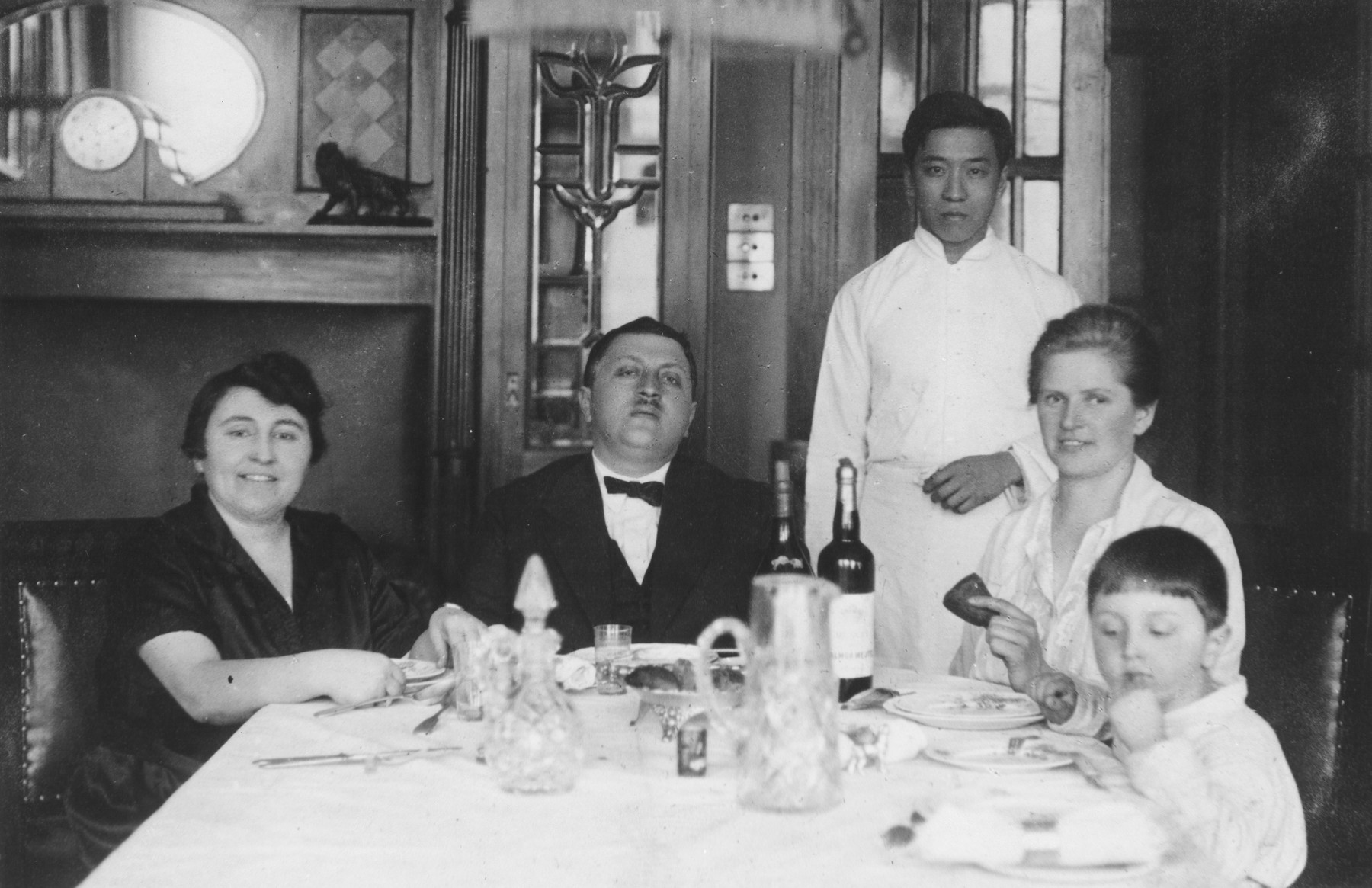 A Jewish family poses with their hired help at the dinner table in their home in Harbin, China.  Pictured from left to right are Betia Faingersch, Aaron Faingersch, their Chinese servant, their German governess and Vladimir Faingersch.