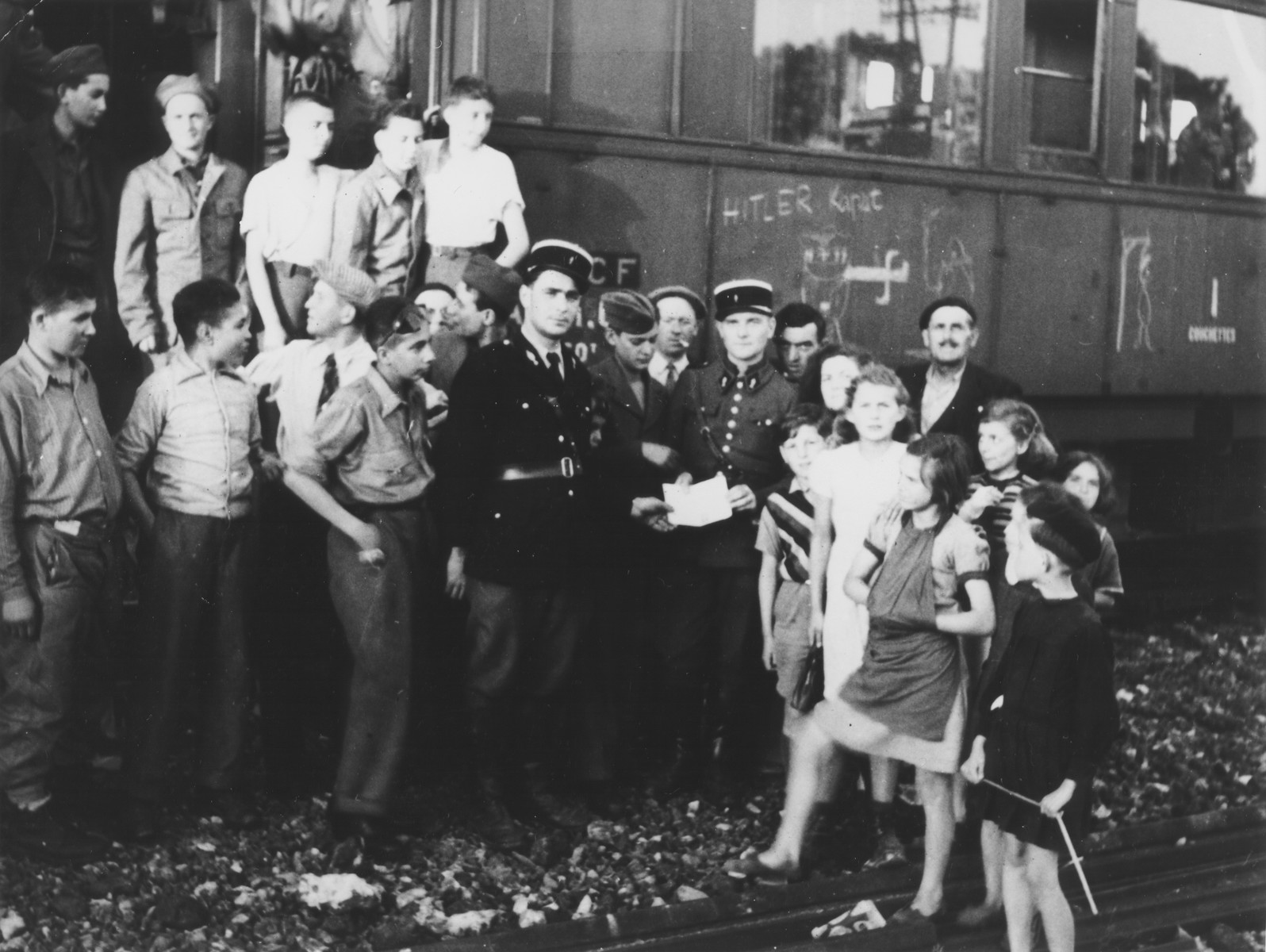 A group of child survivors of Buchenwald pose outside a train that is transporting them to France.