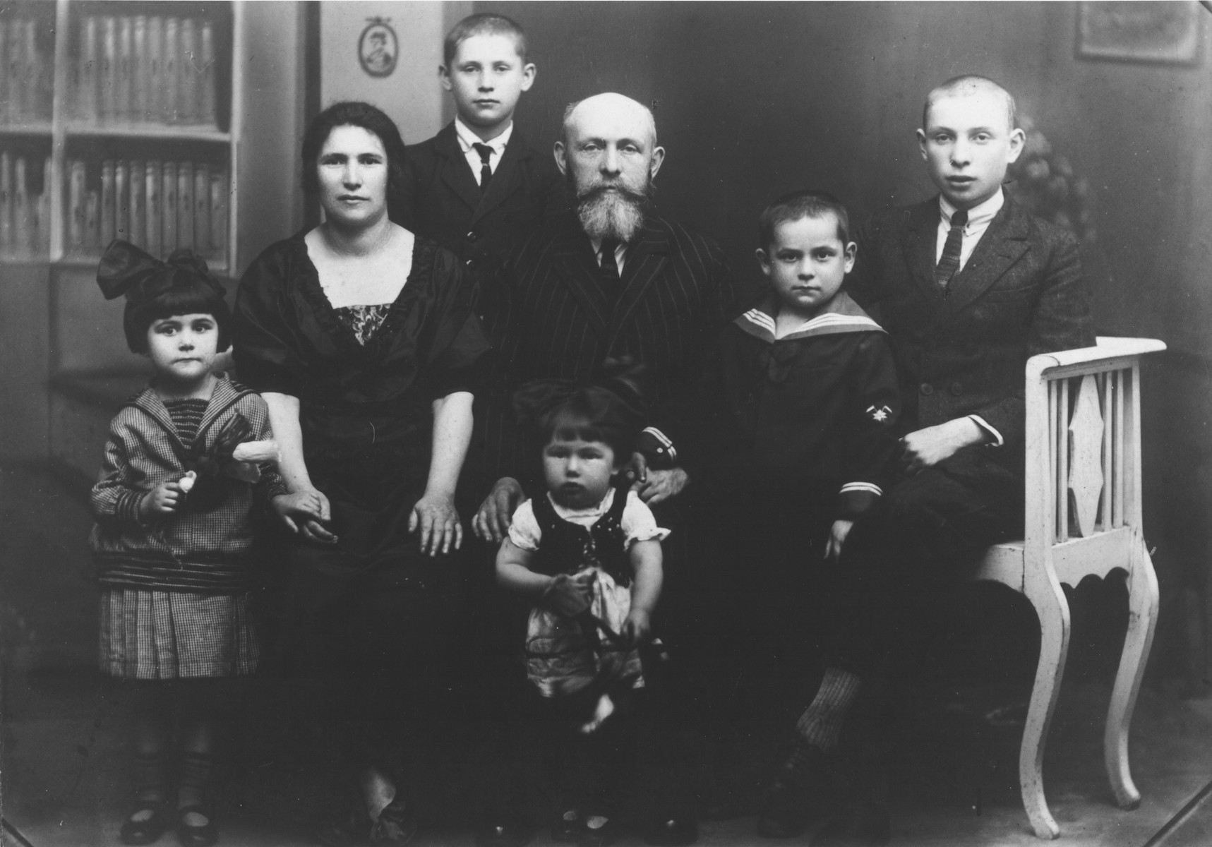 Studio portrait of a Jewish family in interior Poland.  Pictured are Yechial Yosef Szwimer, his wife Raiza  Bella Godfried Szwimer and their children: sons Zvi, Yehuda, Yitzhak or Zerach, and daughters Tova and Rachel. Yechiel was born in Bedzin, Poland to Moshe Yechiel and [mother's name unknown]. Yechiel served  in the RAF in Ramat David in Israel, and died in 1967.   Pictured in the center are Aaronl Szwimer with some of their eleven children.