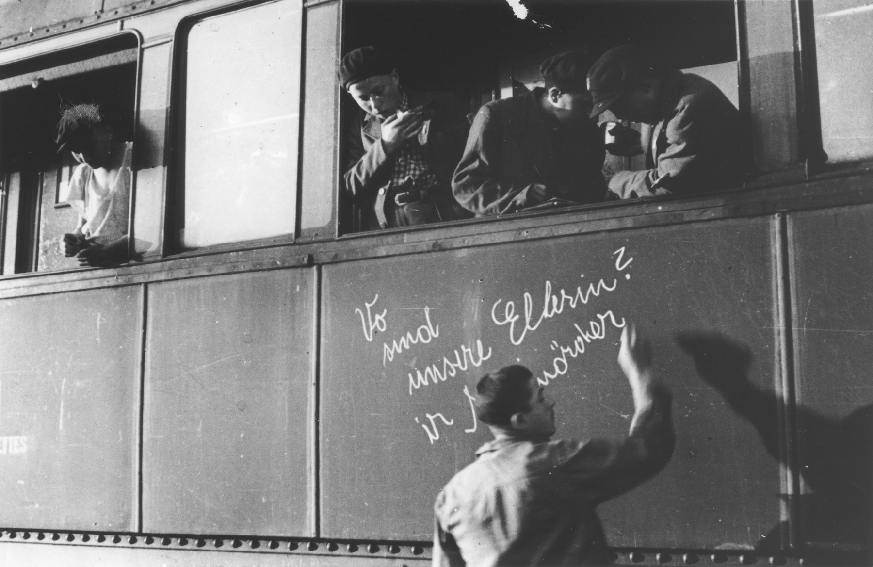 """One of the young survivors of Buchenwald writes in German """"Where are our parents?"""" on the side of a train prior to the departure of the children's transport from Buchenwald for France.  The boy writing on the side of the train is Joe Dziubak from Lodz."""