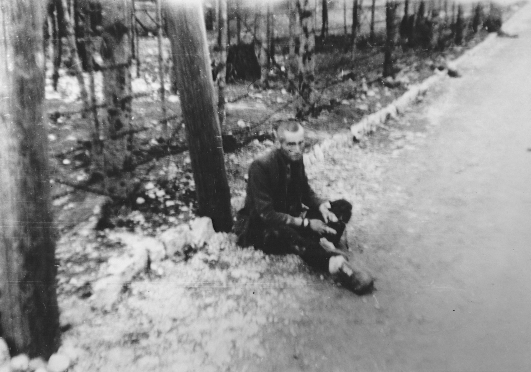 An exhausted survivor sits by the side of a road in the Ebensee concentration camp soon after the liberation.