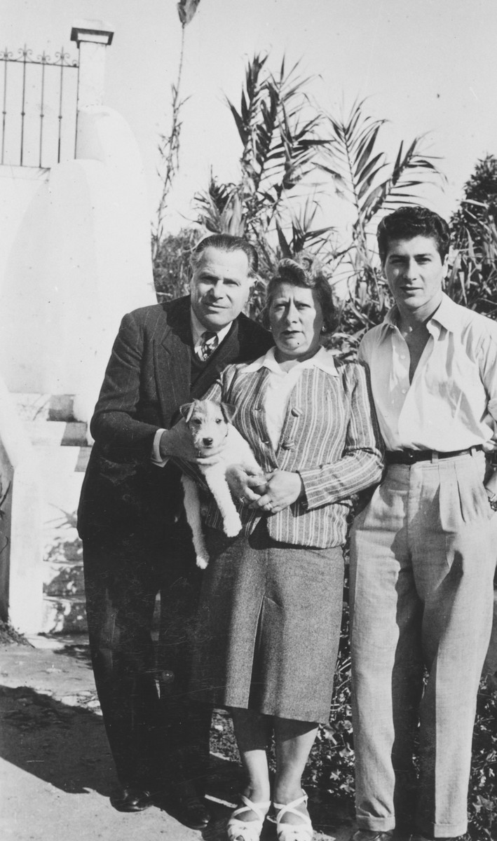 A Jewish refugee family poses outside with their dog in Ericeira, Portugal, after their escape from German-occupied France.