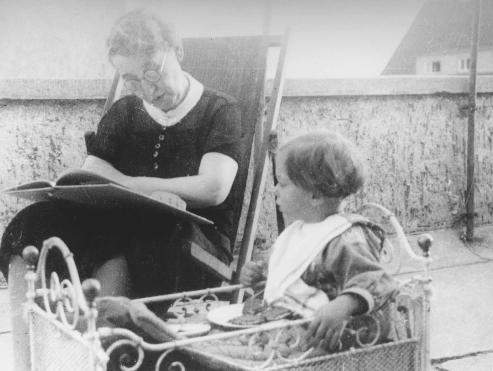 A Jewish woman reads to her granddaughter on the terrace of her home in Kassel, Germany.  Pictured are Mrs. Lindenfeld with Dorrith Oppenheim.