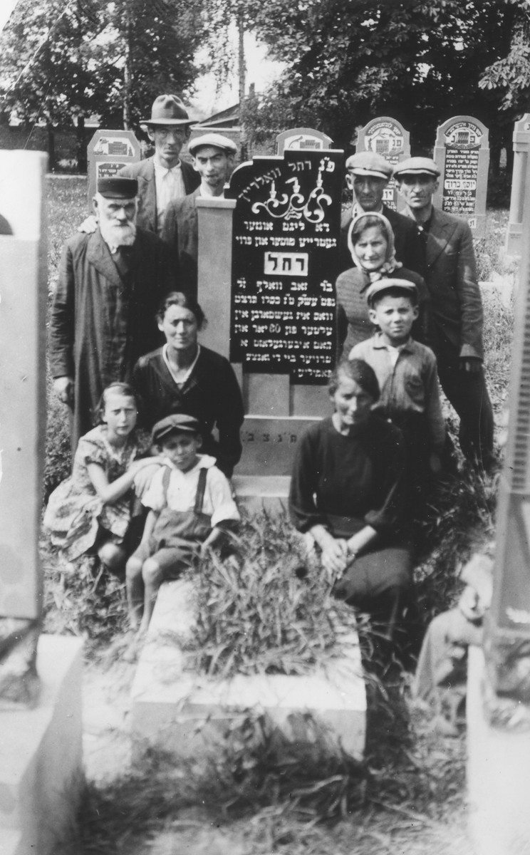 Group portrait of members of an extended Jewish family at the grave of their relative in Piotrkow Trybunalski, Poland.  Pictured are members of the Wolrajch family at the grave of Rachel Wolrajch.  Pictured on the left side, from back to front are: Hersh Lieb, Shaya, Moishe, Aunt Sura, Sura and Velvel,  On the right side are: Avrum, Josef, Zelda, Avrumele and Gietle.