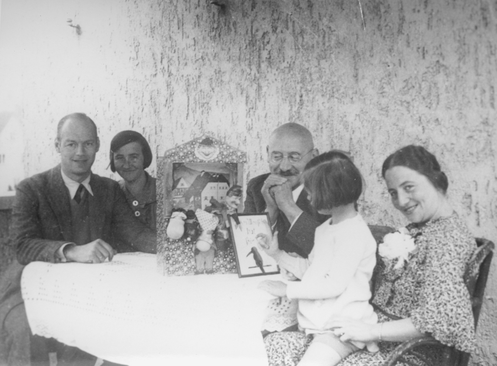 A Jewish family gathers around a table with a Punch and Judy puppet theater in Kassel, Germany.  Pictured from left to right are: Hans, Trudi, Julius, Dorrith and Alice Oppenheim.