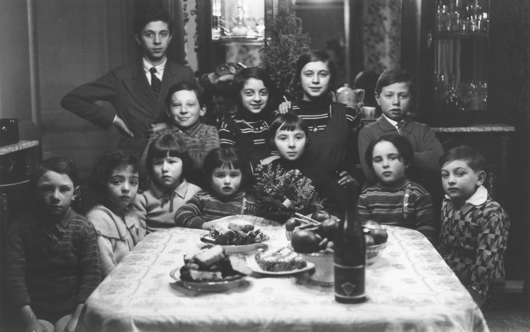 Group portrait of Jewish children gathered around a table at a birthday party in Paris.  Among those pictured are Aba Sztern (second row far right) and his sister Catherine (front row, third from the left), .