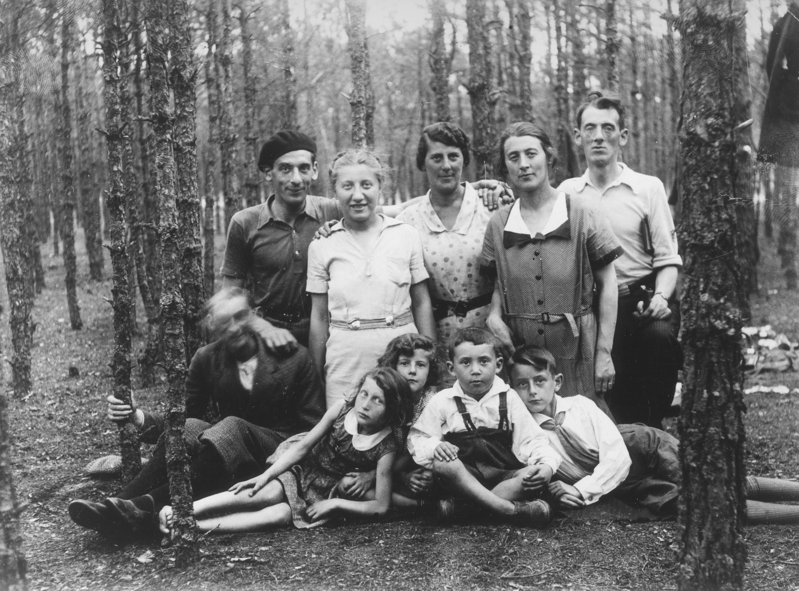 Group portrait of members of an extended Jewish family on an outing to the Wolboz Forest near Piotrkow Trybunalski, Poland.  Pictured are members of the Wolrajch family.  The photograph was taken during the visit of a cousin, Helen Tolep, from the U.S.  Pictured in the back row from left to right are: Joel Wolrajch, Helen Tolep, Rachel Wolrajch (wife of Hersh Lieb), Chia Sura Wolrajch and Hersh Lieb Wolrajch.  Sitting in front are: Shaya Wolrajch (blurred), Rachel Fish, Ginka Wolrajch, wolf, and Chiemic Wolrajch.
