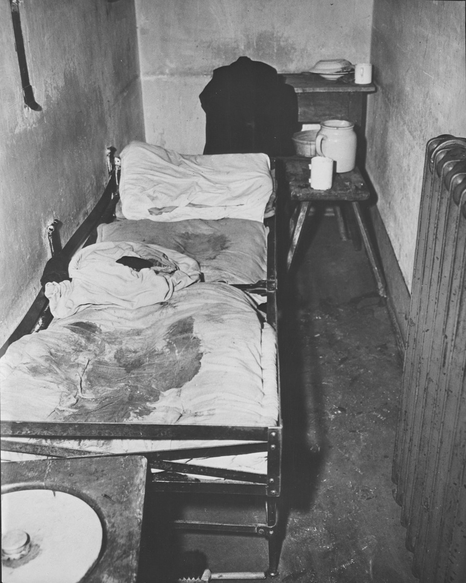 View of a cell in the Gestapo prison in Koeln (Cologne), Germany, where a female inmate was flogged to death.  Allied Military Government officials who liberated the prison report that this is the cot of a young woman prisoner who was stripped and flogged by Gestapo agents, then thrown on the cot to die.  The woman's clothing lies in the center of the bed.  The stain on the mattress in the shape of head, shoulders and torso is her blood.  Of the 80 prisoners found by First U.S. Army troops who captured Cologne March 6, 1945, five were dead, three died the night the Americans arrived, and 31 were hospitalized for malnutrition, fleck fever and typhus.  Most of the inmates had been accused by the Nazis of being members of the underground or of aiding or hiding Russians and Poles.