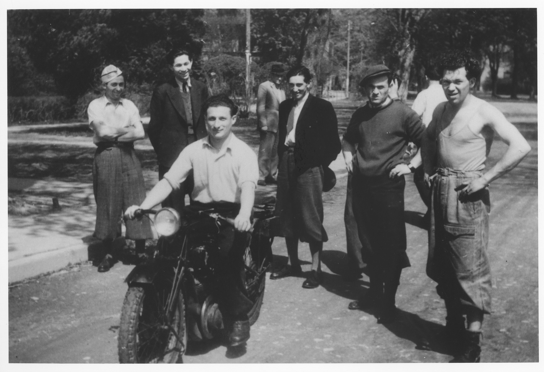 Zdenek Mermelstein rides a motorcycle in the Gabersee displaced persons camp.  Standing second from the left is Asher Zelig Shlomowitz.  Also [probably] pictured second from the right is Mendel Senderovits.