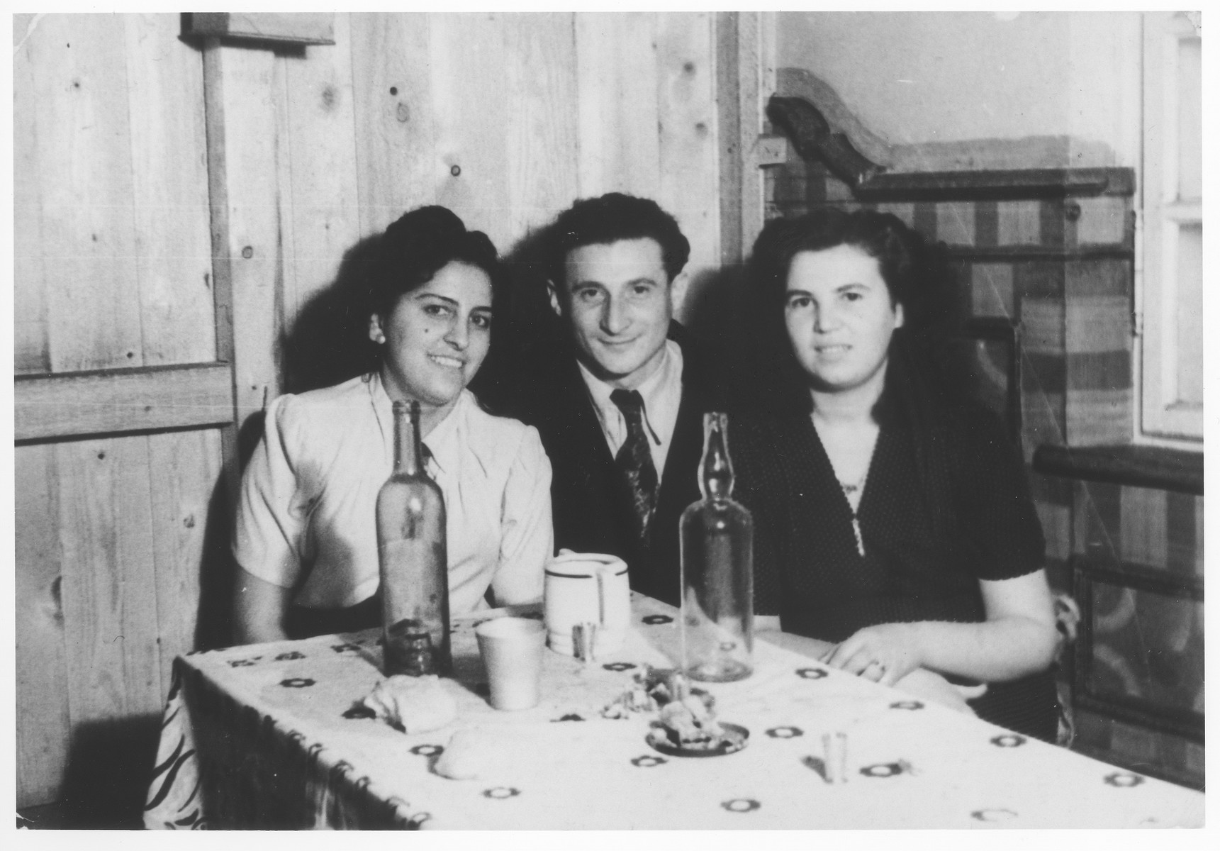Zdenek Mermelstein sits with two young women in a room in the Gabersee displaced persons camp.