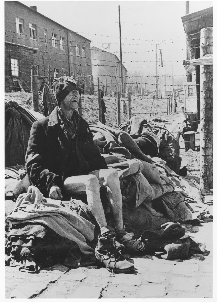Close-up of an emaciated middle-aged survivor, wearing a tattered cap, sits on a pile of blankets alongside a barbed wire fence in Buchenwald.  He had been imprisoned in Buchenwald for seven years.  Behind him, another survivor rests on the same pile.