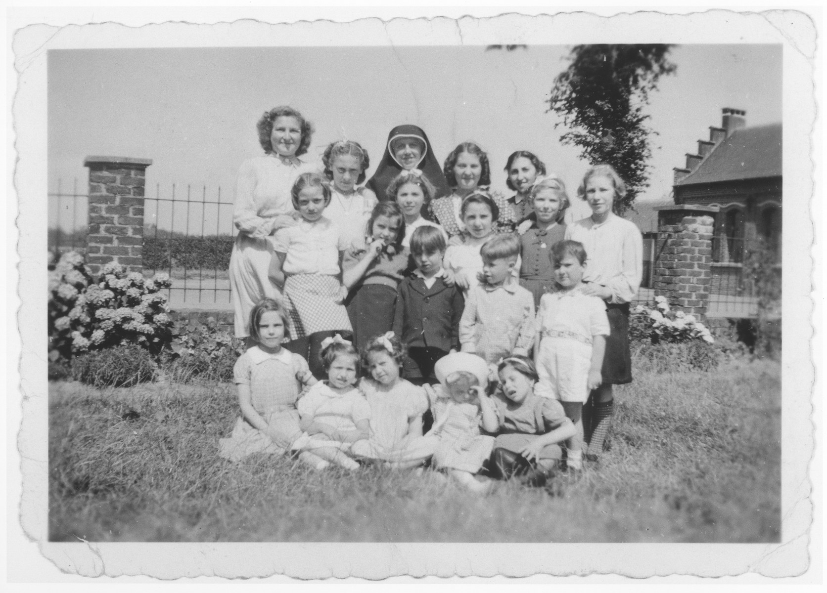 Sister Huberte poses with a group of children, many of whom are Jewish children in hiding, at the Soeurs de Sainte Marie convent near Braine-l'Alleud.  Ursula Klipstein is pictured in the top row, fourth from the left.