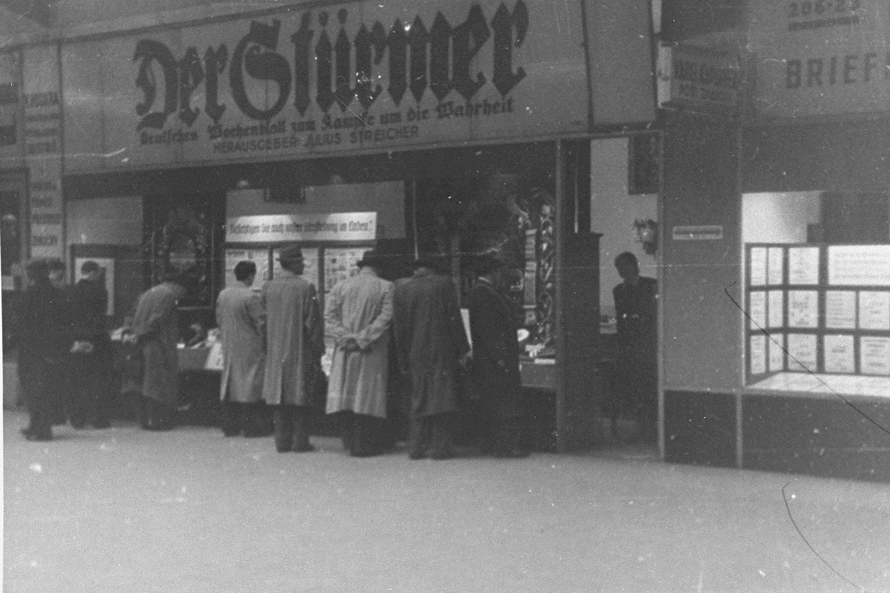 "Czech civilians look at a display box beneath a ""Der Stuermer"" sign in occupied Czechoslovakia."