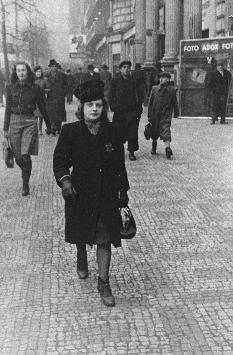 Elsa Eisne (the donor's aunt) walks down a street in Prague wearing the Jewish badge.    Elsa, her mother, twin sister Klara, and other relatives were deported to Auschwitz in July 1942.  The donor's father, Joseph, was the husband of a German Christian woman, Maria.  Joseph and his son, Al, were deported to Theresienstadt and interned there until the camp was liberated by the Red Army on May 9, 1945.