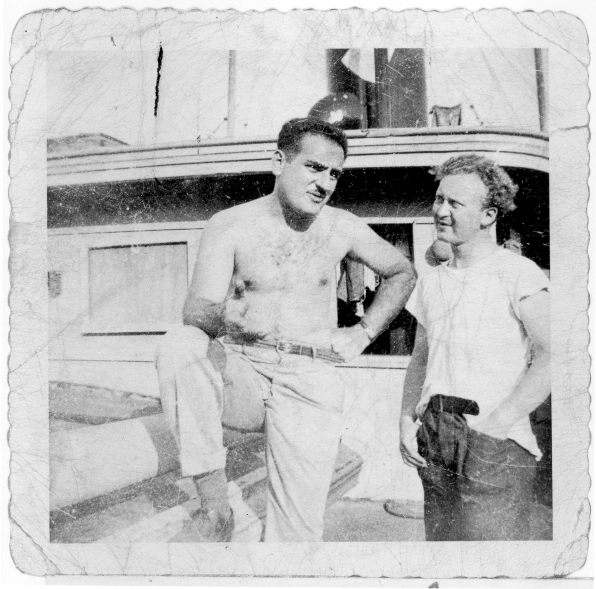 Eli Kalm (left) and William Bernstein, crew members of the President Warfield/Exodus 1947, converse on the deck of the ship before its departure for Europe.