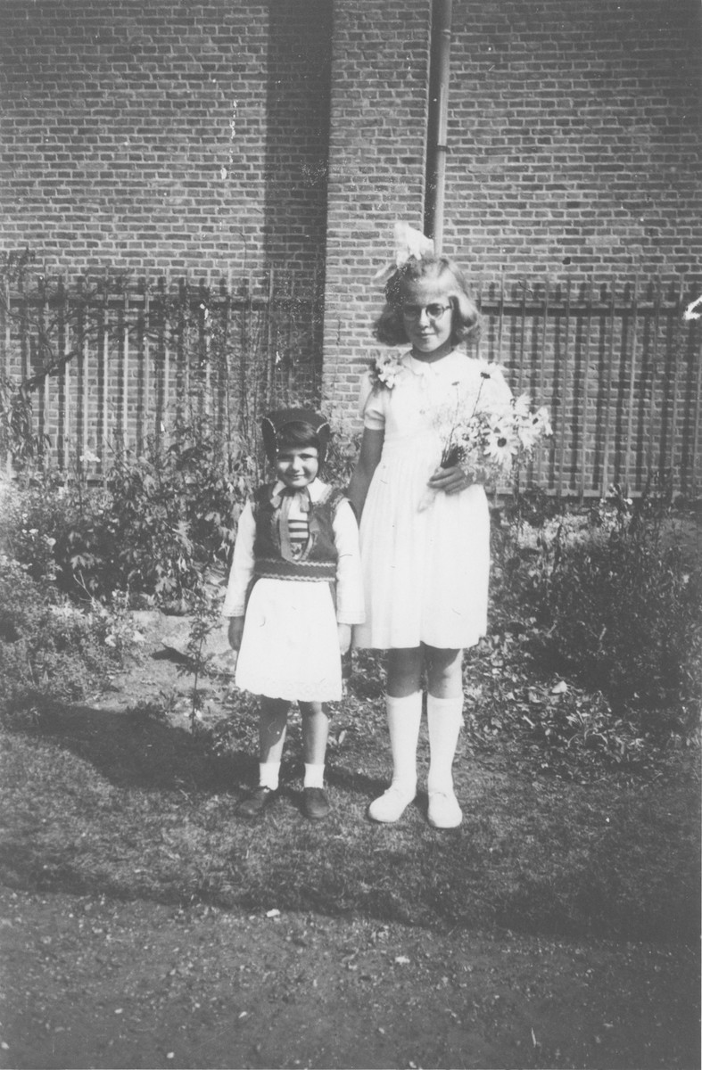 A Jewish child in hiding poses with the daughter of her Dutch rescuer in Laren, Holland.  Pictured at the left is Elizabeth Reiss, the Jewish child, and on the right, Lili Salters, the youngest daughter of Antonius and Marie Salters.