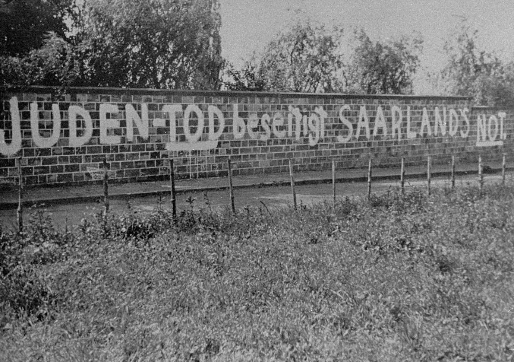"The anti-Semitic graffiti painted on the wall of the Jewish cemetery reads, ""The death of the Jews will end the Saarland's distress."""