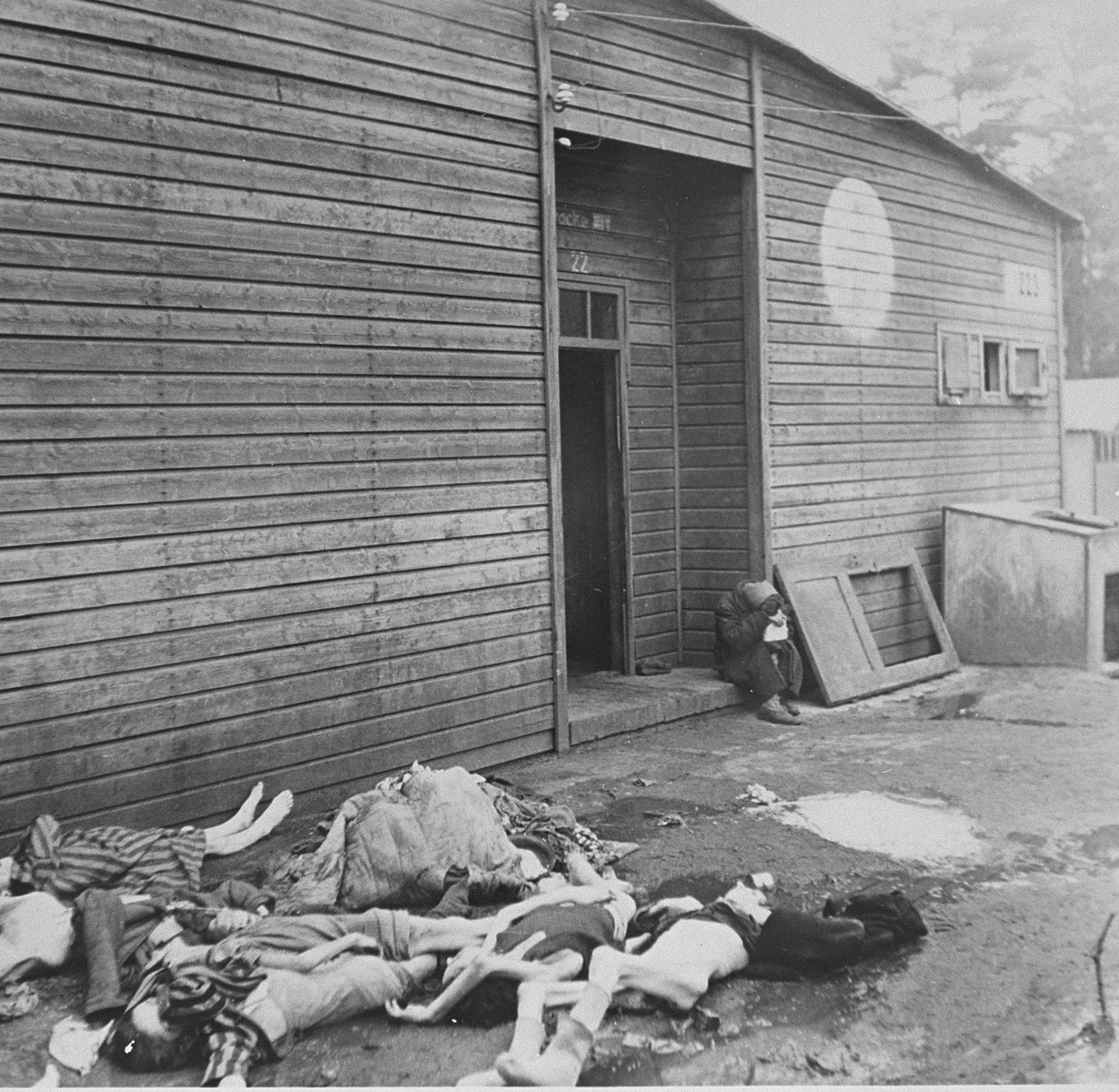 Corpses lie on the ground outside of the infirmary in Bergen-Belsen.