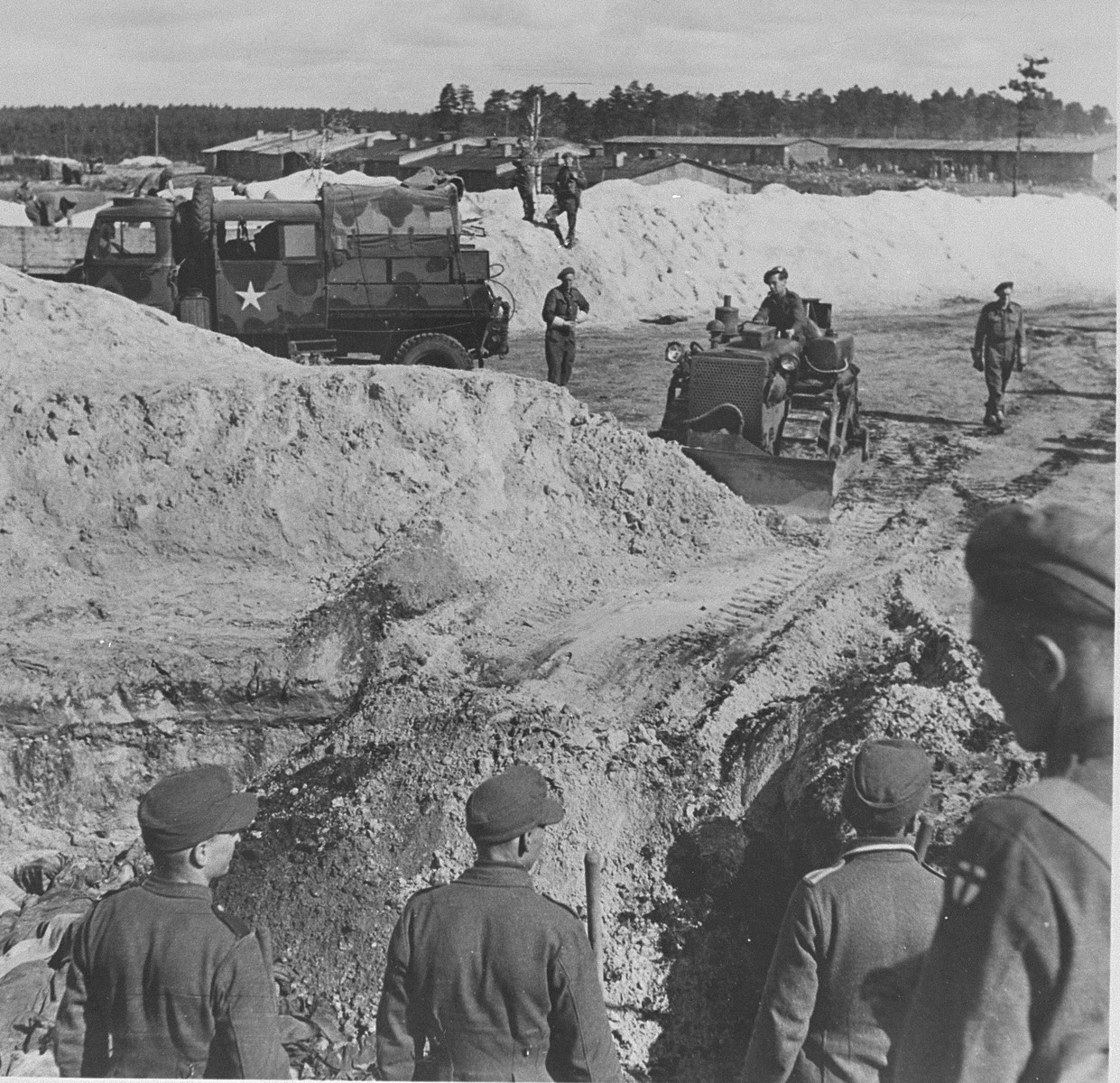 A British bulldozer closes a mass grave at Bergen-Belsen while former camp guards look on.