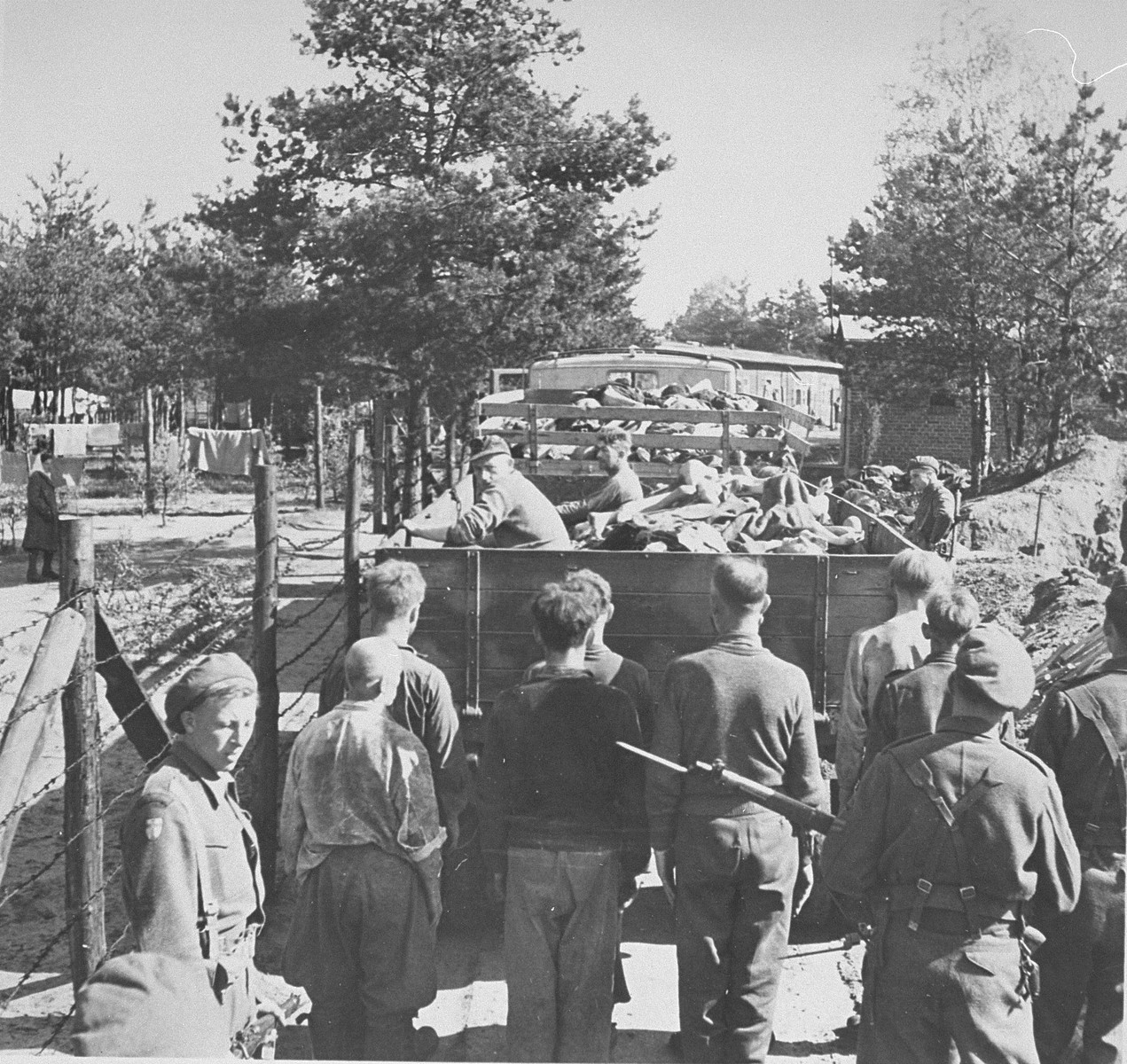 British soldiers transport former SS guards and truckloads of corpses to mass graves for burial.    Former camp doctor Fritz Klein can be seen seated in the back of the lorry.