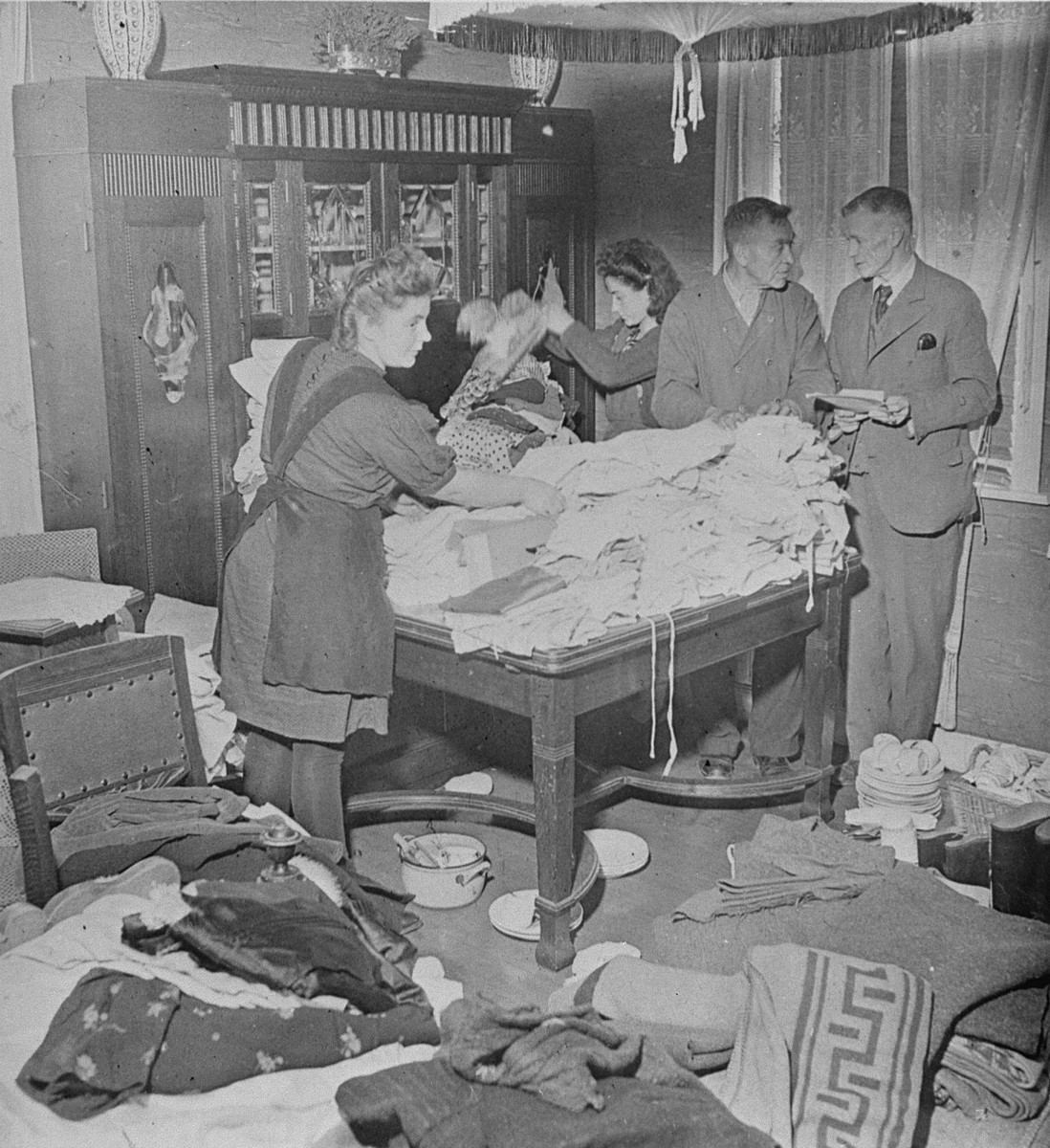 Ilse Kohra(L), the daughter of the Burgermeister of the German town of Belsen, along with Herr Pfeifer(R) and his daughter Anna, sorting clothing for Bergen-Belsen survivors in the Burgermeister's house.