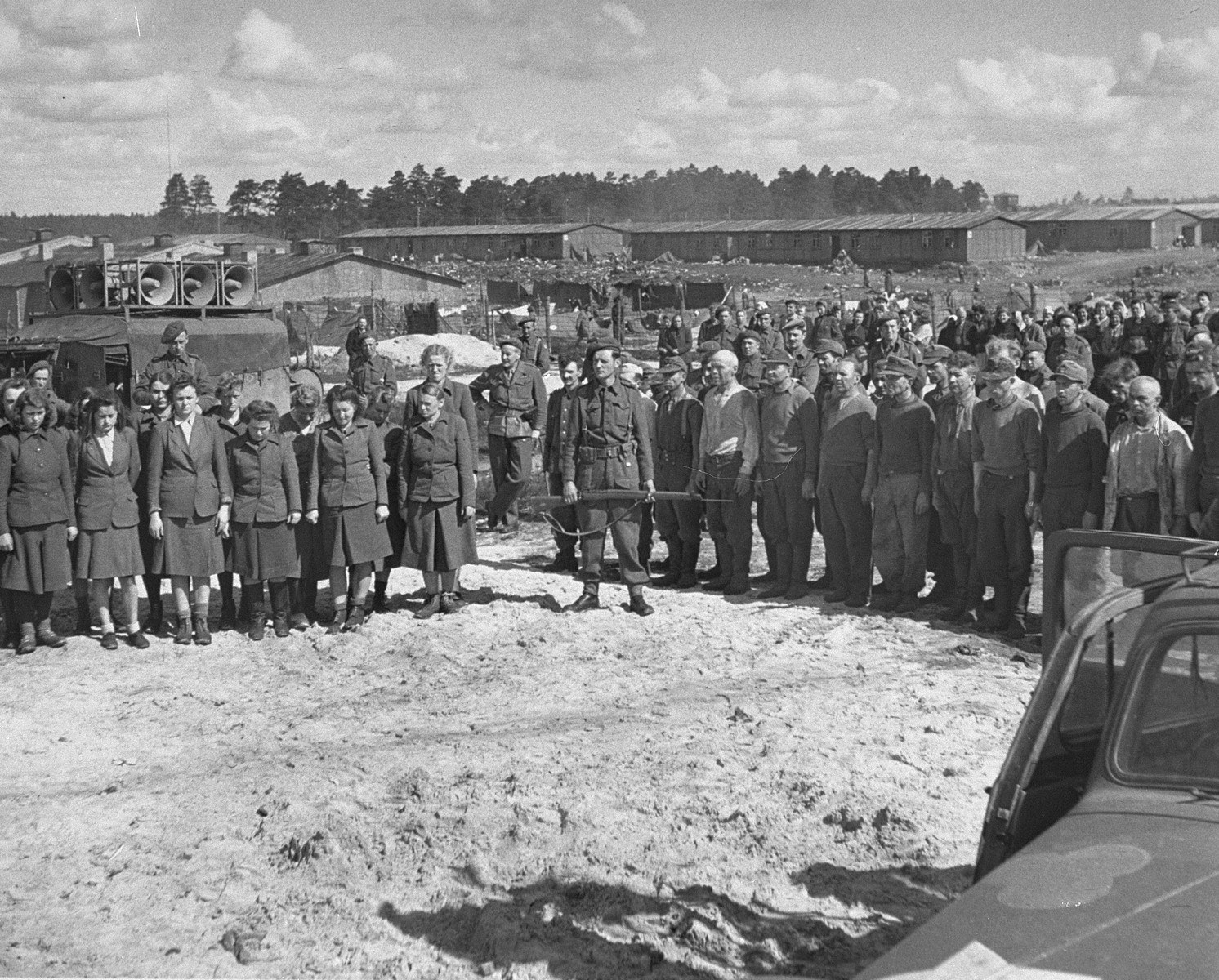 The barracks of Bergen-Belsen concentration camp visible behind them, male and female camp personnel are lined up in front of a mass grave to hear a broadcast denouncing the Germans and their treatment of prisoners.