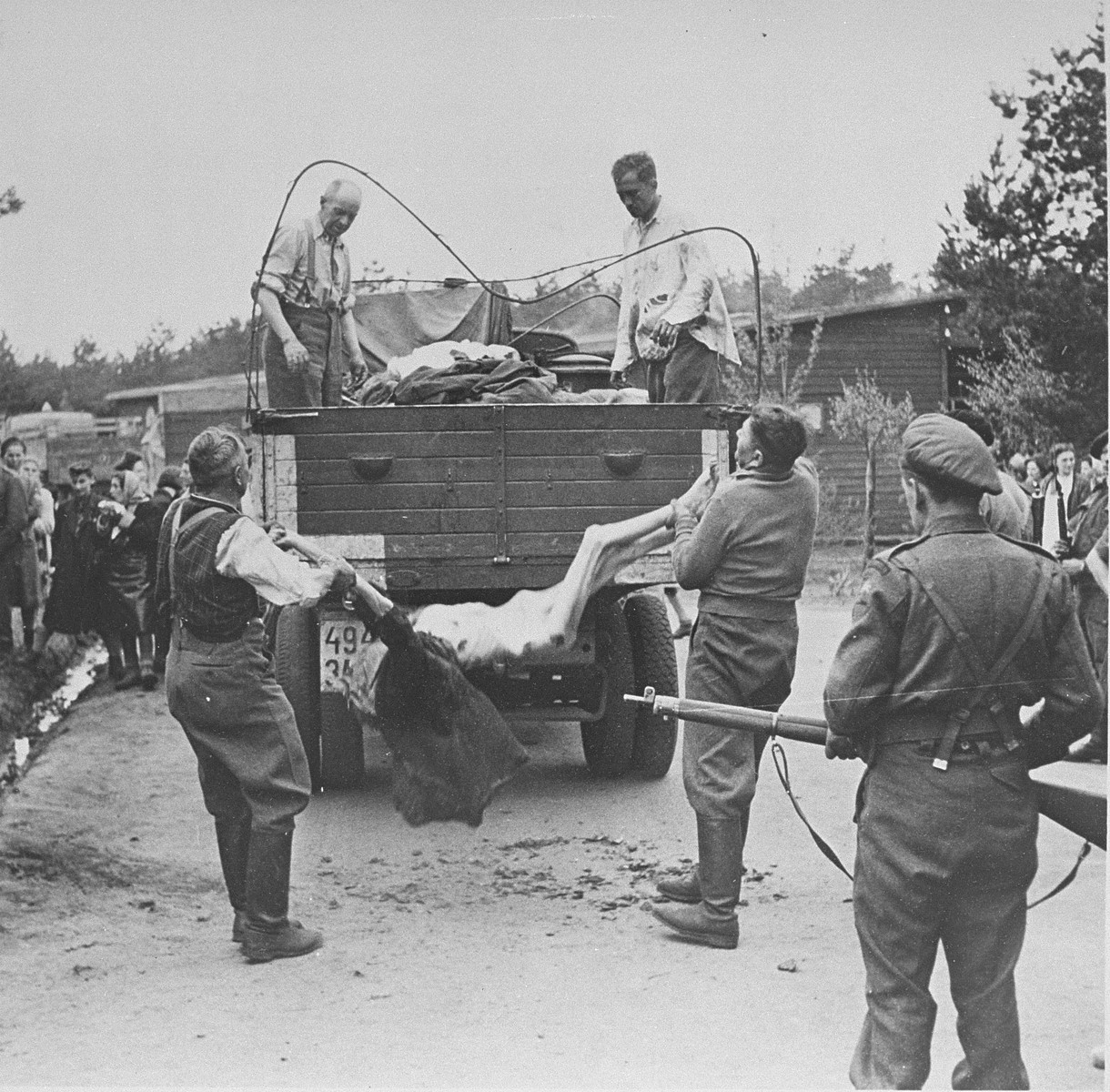 "SS guards are forced to load corpses onto a truck while under the supervision of British soldiers.  Original caption reads:  ""S.S. men captured at the camp, are made to load lorries with bodies to be taken away for burial."""