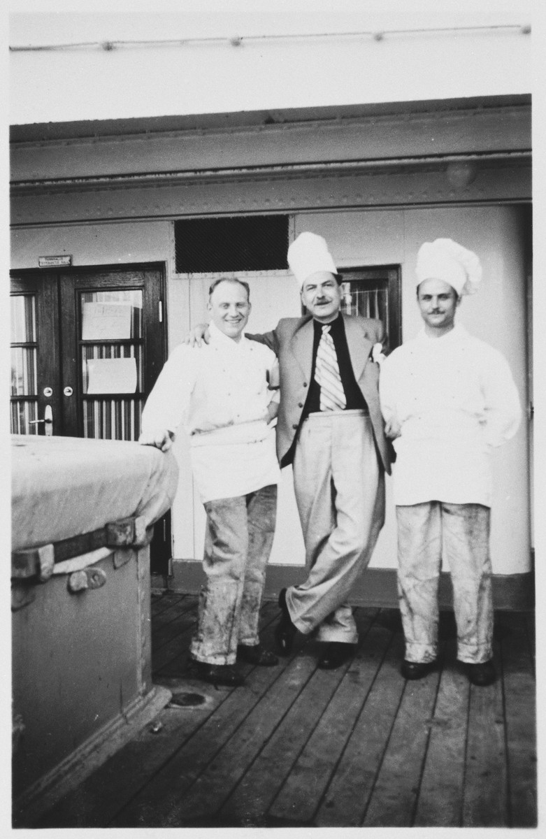 Three chefs aboard the MS St. Louis pose on the deck of the ship.
