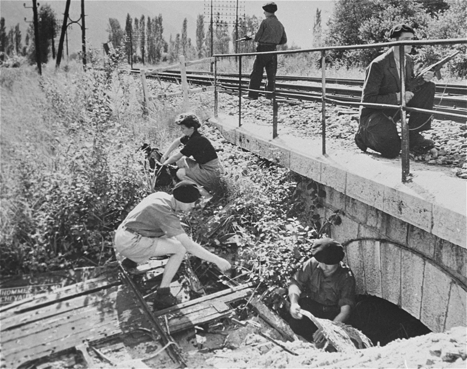 Members of the Maquis of Voireppe in the Chartreuse Region of the French Alps demonstrate the method used to place dynamite demolition charges under a railroad trestle to delay Nazi supplies.