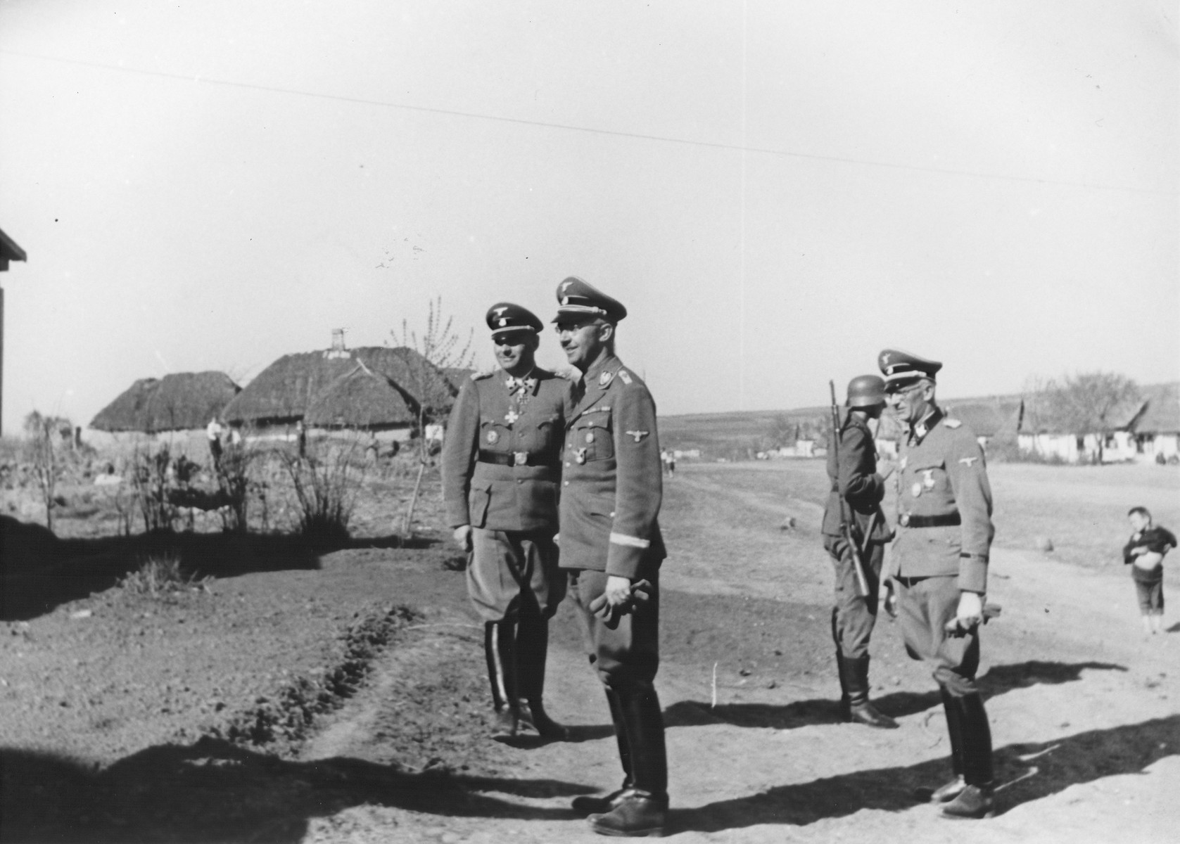 Reichsfuehrer-SS Heinrich Himmler stands outside with leaders of the Waffen-SS Armored Division Wiking during an official visit.  SS-Obergruppenfuehrer and General Herbert O. Gille (commander of the Wiking Division from May 1943 until August 1944) is pictured at the right wearing glasses.