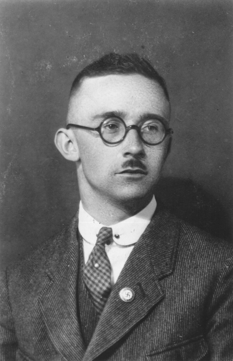 Studio portrait of Heinrich Himmler wearing a Nazi party pin on his lapel.