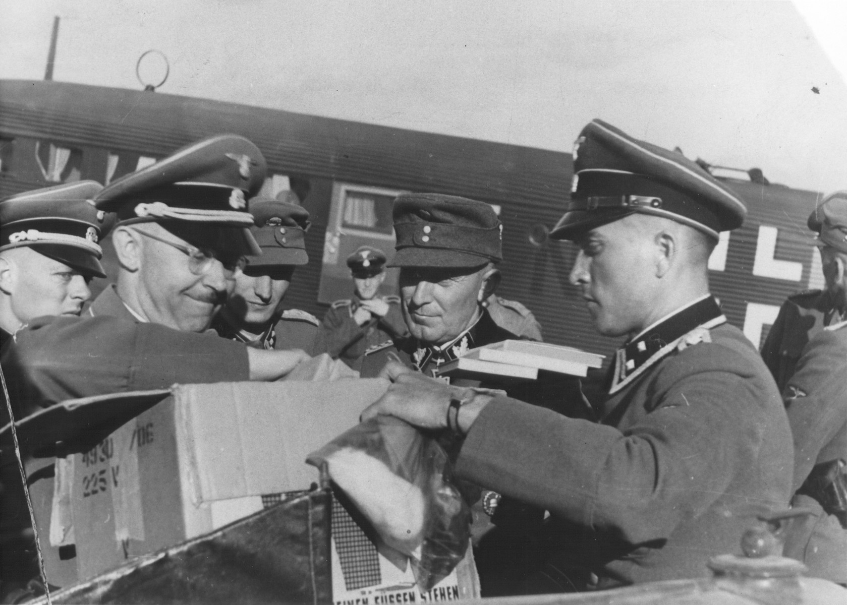 Reichsfuehrer-SS Heinrich Himmler pulls items out of a cardboard box at an airfield in the Karelia region of Finland.  Among those pictured is SS-Sturmbannfuehrer Werner Grothmann on the far left.  Pictured second from the right is Matthias Kleinheisterkamp.   Matthias Kleinheisterkamp was an SS-Brigadeführer at the time the photo was taken He is wearing the Knight's Cross of the Iron Cross beneath his collar which he received in early 1942, in connection with his leadership of the SS Das Reich Panzer division on the Eastern Front.