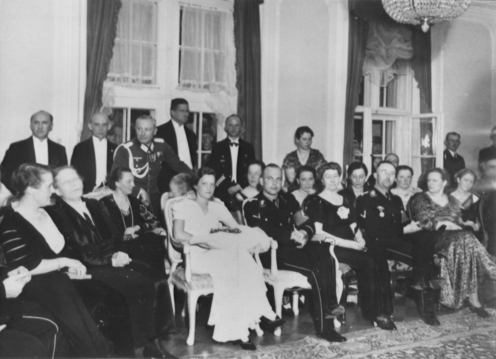 Reichsfuehrer-SS Heinrich Himmler attends the wedding of Hans-Adolf Pruetzmann.  Himmler and his wife, Margarete, are seated in the front row at the right.