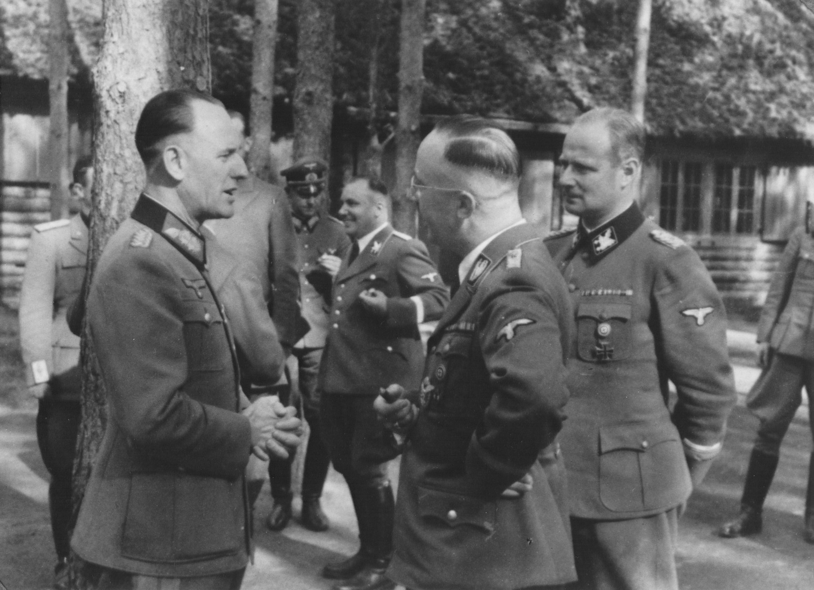 Reichsfuehrer-SS Heinrich Himmler converses outside with Rudolf Schmundt at Wolfsschanze (Wolf's Lair), Hitler's field headquarters in Rastenburg, East Prussia.   Pictured in the foreground from left to right are: Rudolf Schmundt, Heinrich Himmler and Karl Wolff.  Also pictured is Martin Bormann (in the background without a hat, between Schmundt and Himmler).